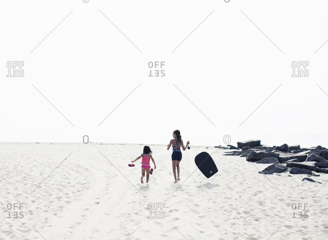 Young girl carrying body board and sister race each other across the beach to the sea