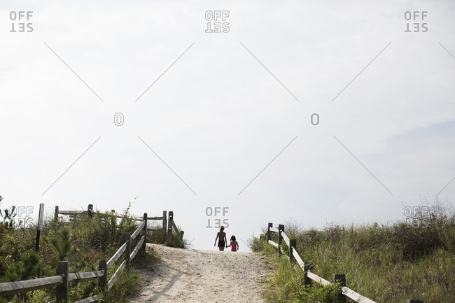 Young girl and sister holding hands as they disappear over dune to the beach