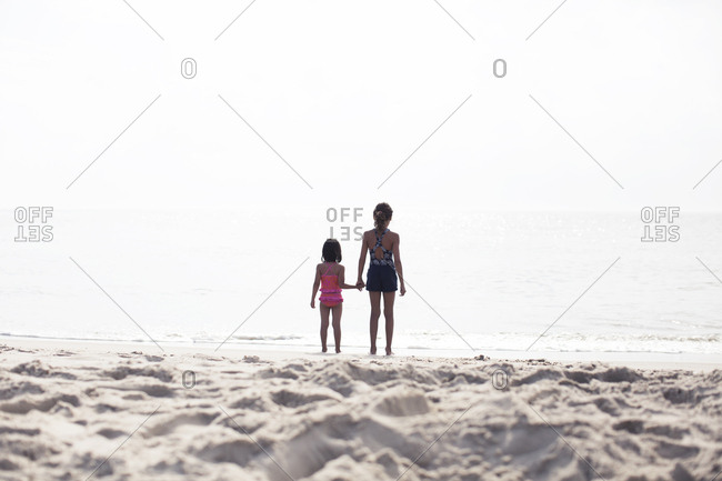 Young girl and sister at the beach holding hands as they look out to sea