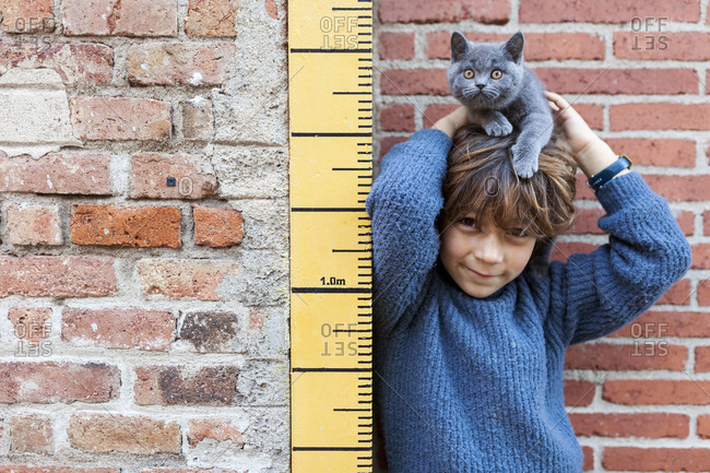 Boy standing next to growth chart holding his pet kitten on his head