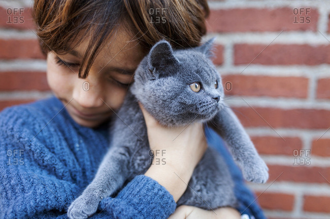 Boy snuggling with his pet kitten
