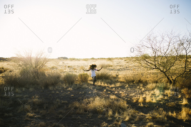 Girl running through the desert landscape