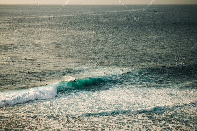 Distant view of surfers riding waves in the ocean
