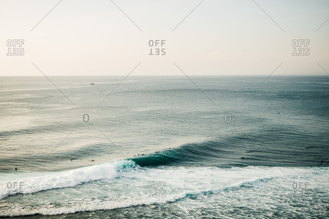 Distant view of surfers waiting for waves in the ocean