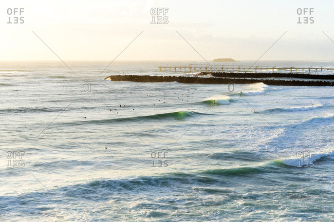 Distant view of surfers in the ocean near jetty
