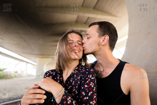 Smiling woman being kissed by her boyfriend