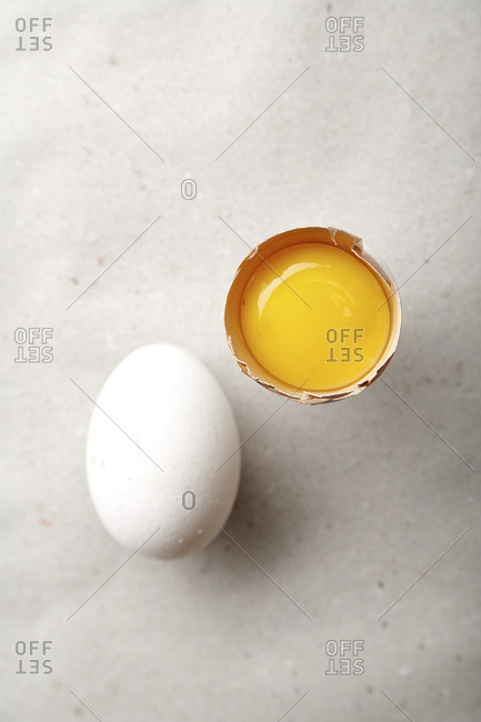 White chicken egg with one egg yolk on paper sheet