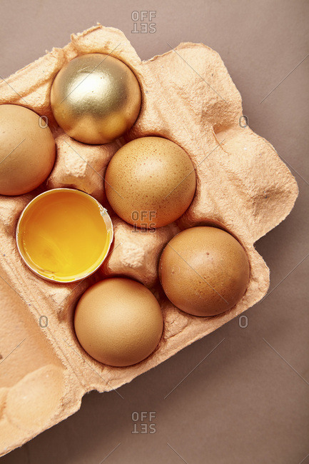Horizontal close-up shot with colorful cardboard container of pink color with chicken eggs, one yolk visible, one egg painted golden. Easter concept