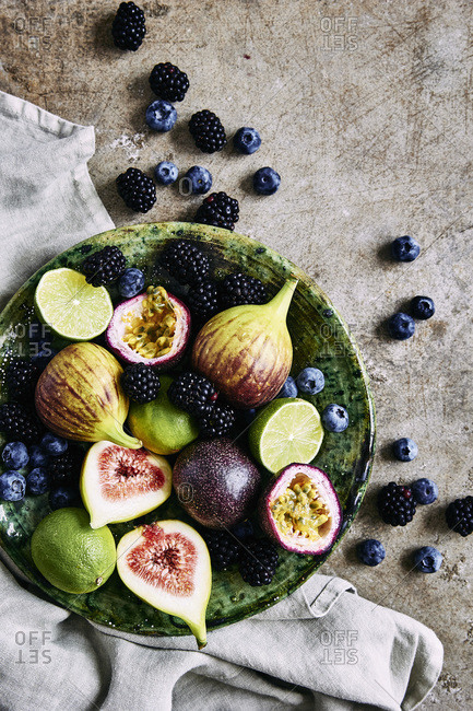 Fresh fruit platter, with figs, limes, blueberries, blackberries, and passion fruit.