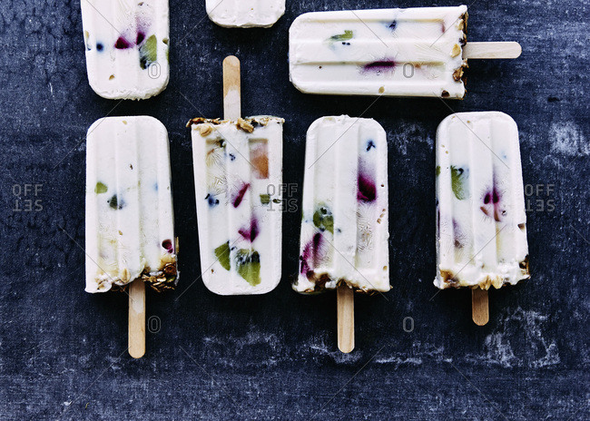 Yogurt and summer fruit popsicles topped with muesli granola. botanical ice blocks of edible flowers and herbs.