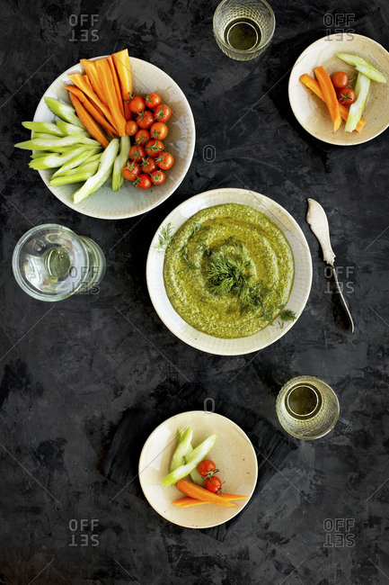 Bowl of dill pesto served with veggies and white wine