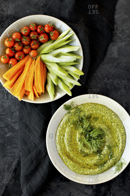 Bowl of dill pesto served with veggies on a black countertop