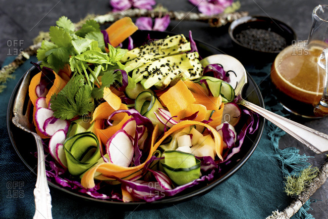 A beautiful place setting of vegetable ribbon salad with toasted sesame vinaigrette