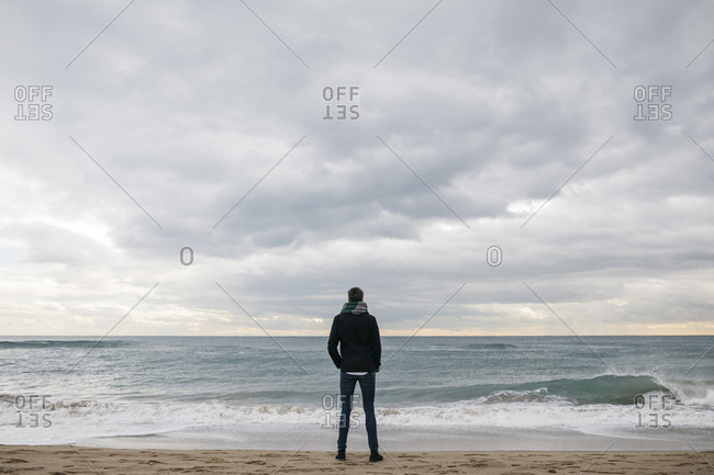 Back view of man standing on the beach in winter looking at distance