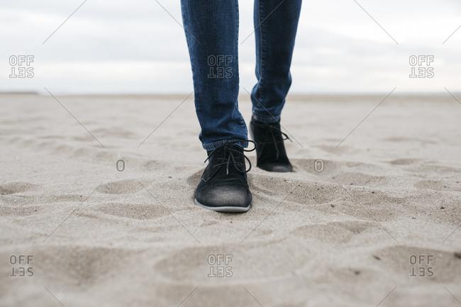 Legs of man walking on the beach
