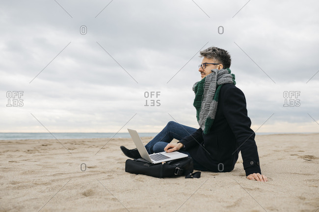 Businessman with laptop sitting on the beach in winter