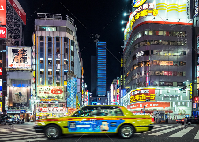 Tokyo, Japan - January 26, 2018: Tokyo, Japan - January 19, 2018: Yellow taxi car driving on crossroad in Asian metropolis at night