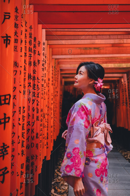 Tokyo, Japan - January 26, 2018: Tokyo, Japan - January 19, 2018: Young pretty Asian woman in traditional clothes standing at red posts with hieroglyphs