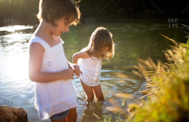 Two little girls standing on shore and in lake together