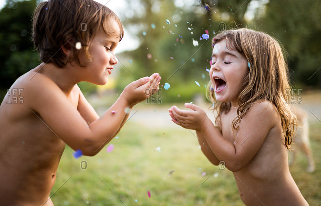 Adorable children playing with confetti on green meadow together