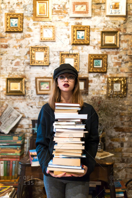 Young pretty woman standing with stacked books in library and looking at camera