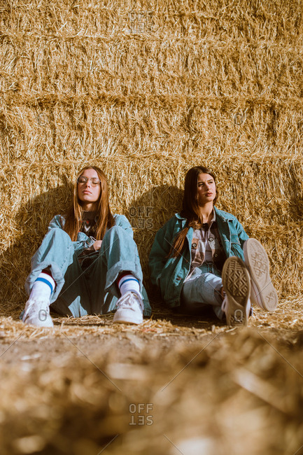 Young women sitting and leaning on hay in countryside together