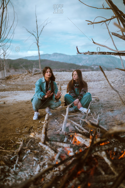Pretty young women sitting together and warming at bonfire in nature