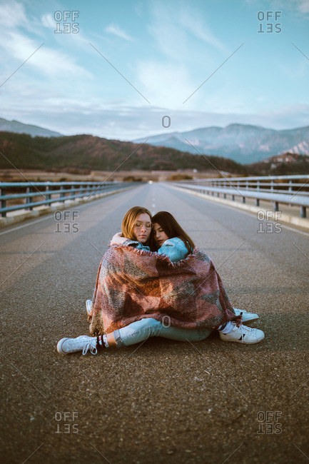 Young pretty women couple wrapped in plaid sitting and embracing on road