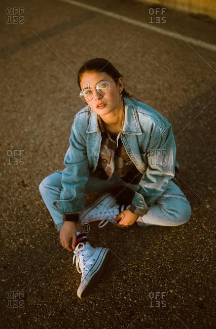 Pretty woman sitting on asphalt road