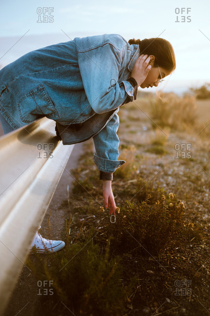 Side view of pretty young woman touching grass at road in countryside