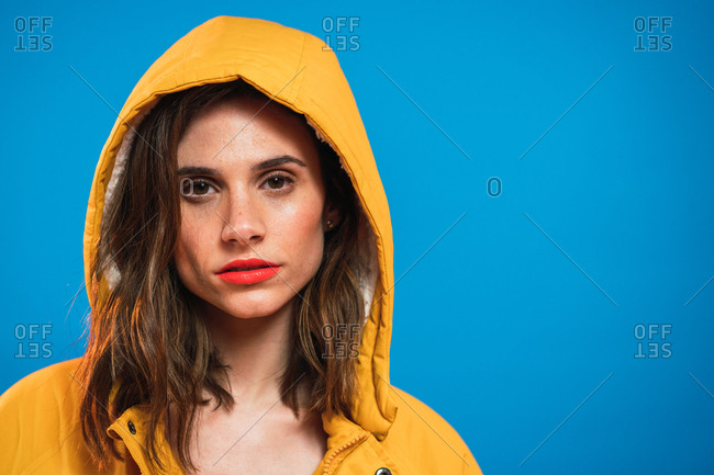 Pretty young woman in hood looking at camera on blue background