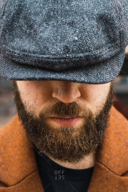 Close-up bearded man in cap and coat on city street