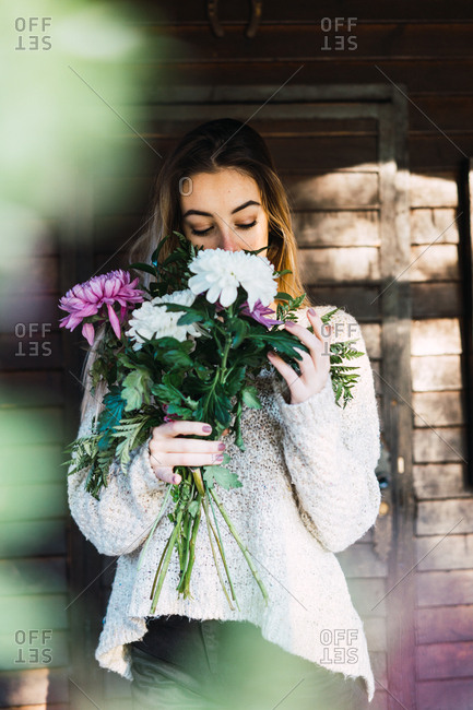 Beautiful content model in sweater smelling bunch of flowers standing on house porch
