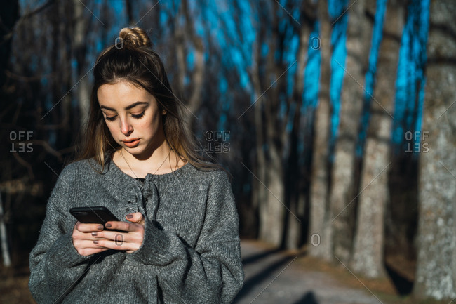 Woman with phone on nature