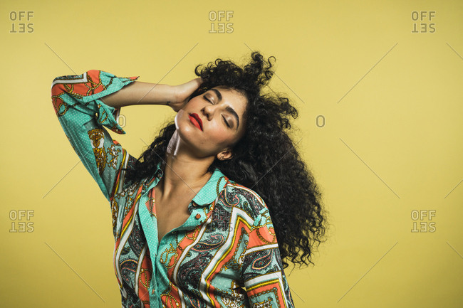 Sensual attractive woman posing with eyes closed and holding curly hair on yellow background