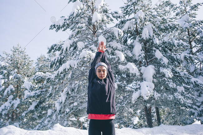 Young woman does exercise in snowy area