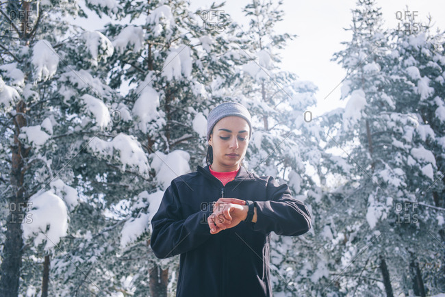 Young woman looks at snowy zone sports watch