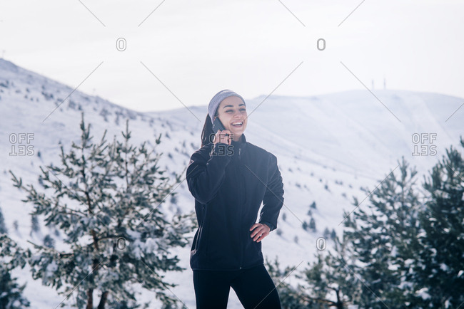 Young sportswoman uses mobile phone in snowy area