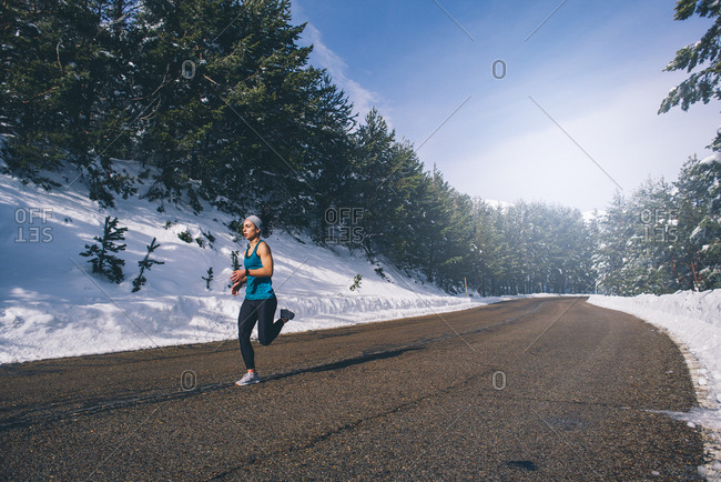 Young woman running in snowy area