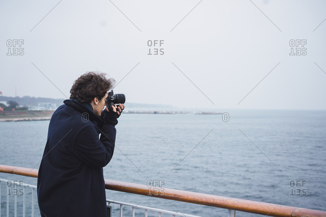 Back view of stylish young photographer man taking shots of the ocean