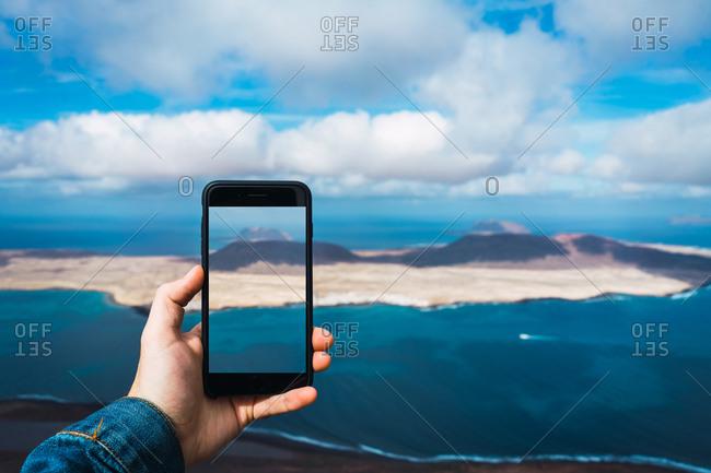 Unrecognizable tourist taking shot of small island in blue sea with smartphone in Lanzarote, Spain