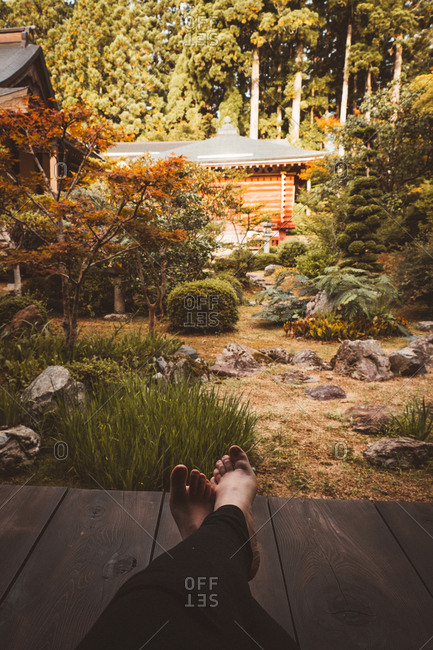 Legs of unrecognizable person sitting and resting in traditional Asian garden