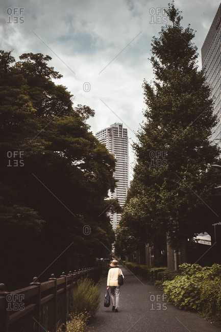 Back view of woman walking in alley with woods in modern city