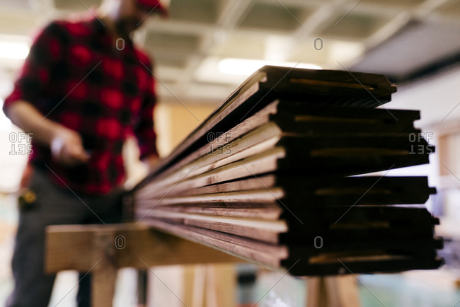 Unfocused carpenter carrying wood