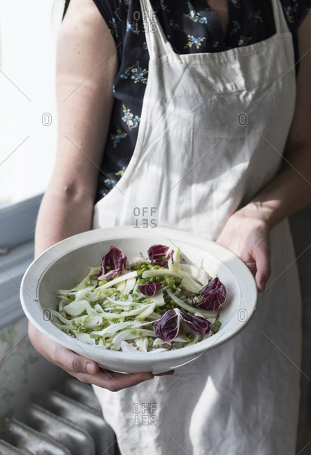 Unrecognizable woman in apron holding bowl of fresh mixed salad