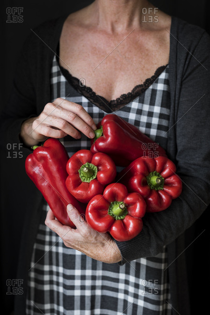Woman holding beautiful fresh red peppers