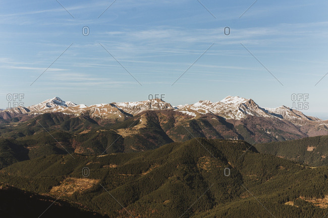 Panoramic view of green mountains with snowy peak on background of blue sky
