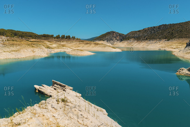 Blue lake in mountains in cloudless sunny day