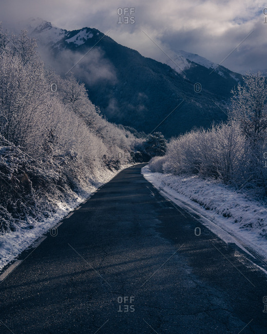 Small asphalt road in snowy winter mountains in countryside