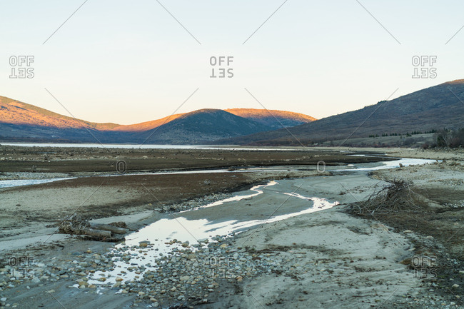 View of gray land with shallow water on background of mountains